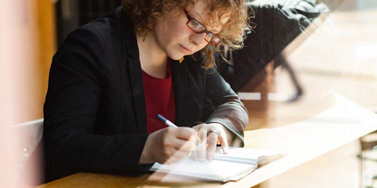 Bild: Franziska Baum schreibt in ein Notizbuch